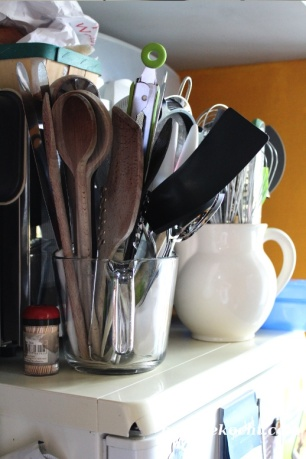Krüge mit Küchenutensilien