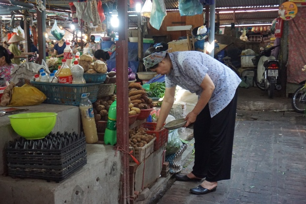 Vietnamesische Frau gebückt über Angebot am Gemüse Marktsstand