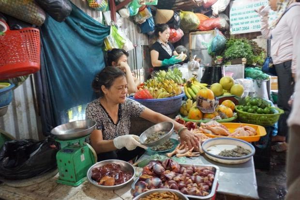 Vietnamesische Marktfrau am Marktstand