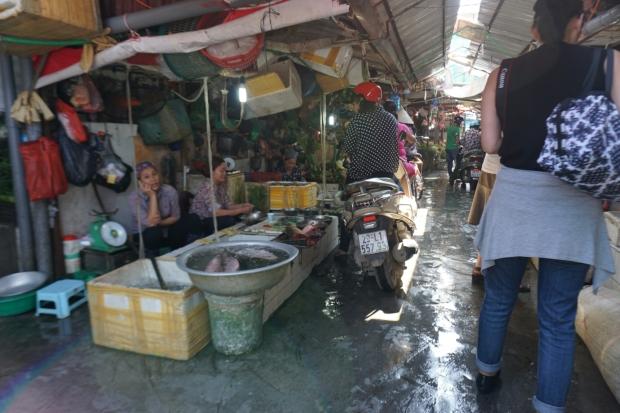 Gasse in Markthalle mit Fischverkauf händler und kunden auf Motorroller