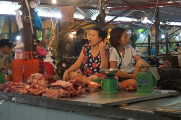 Zwei Marktfrauen hocken entspannt auf dem Fleischttisch und diskutieren