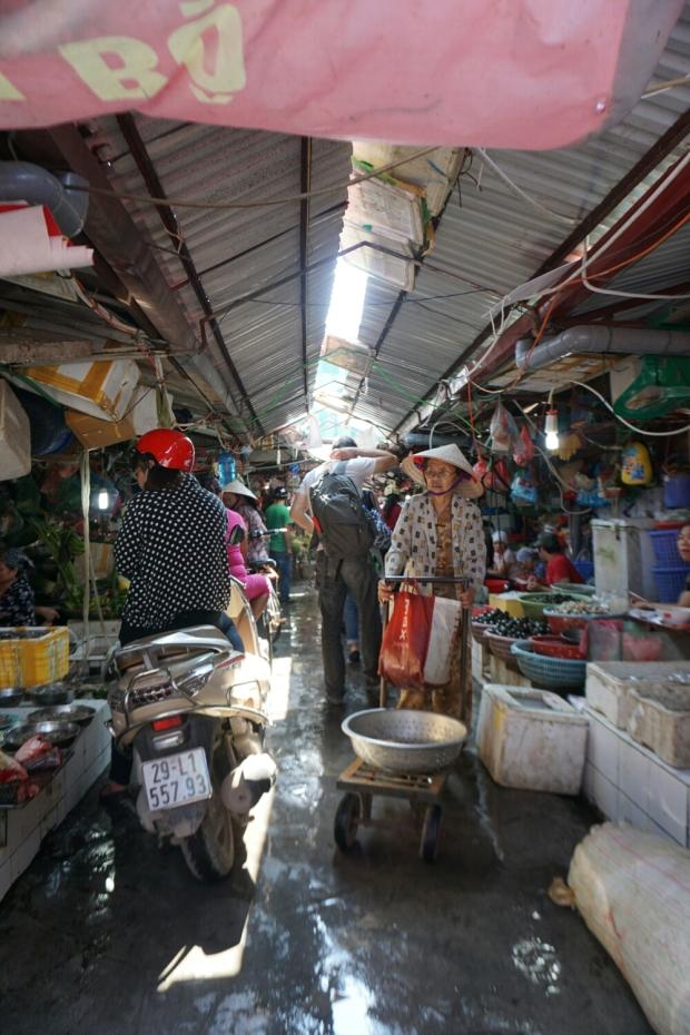 Gasse im Markthalle mit Marktstände, Kunden auf Roller, Verkäuferinnen und Waren