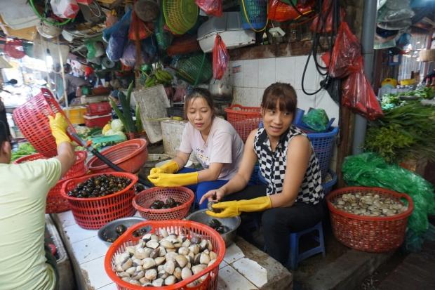 Zwei vietnamesische Frauen beim Muscheln preparieren