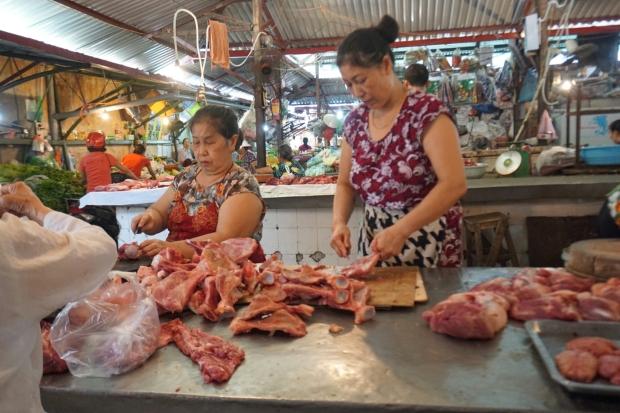 Zweit vietnamesische Marktfrauen beim parieren und verkaufen von Frischfleisch